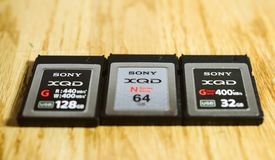 Three new XQD memory card by Sony  on wooden table. PARIS, FRANCE - MAR 26, 2017: Three generations of Sony XQD M, G, G 2 data memory card made by SONY used in Royalty Free Stock Photography