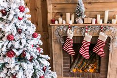 Three New Year`s boots hanging near the fireplace near the Christmas tree. Christmas stock photos