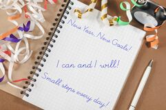 Three new year`s motivational quotes in an open notebook lying on the table.