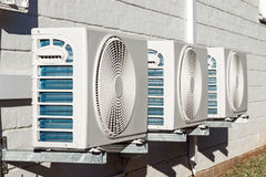 Three Newly Installed Airconditioning Units Mounted on Wall. Three newly installed airconditioning units mounted on exterior wall Royalty Free Stock Photos