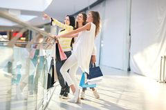 Three nice girls dressed in stylish casual clothes holding lots of shopping bags stand on the second floor of a mall stock image