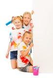 Three nice girls pose near wall Stock Photography