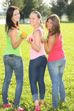Three nice girls posing with fruits in the park Royalty Free Stock Photos
