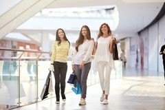 Three nice joyful girls dressed in nice casual clothes walk with lots of shopping bags in the mall. Shopping time stock photography
