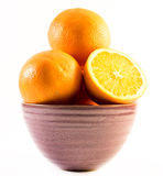 Three nicely colored oranges in a cup on a white background - front and back cut in half.  Royalty Free Stock Photography
