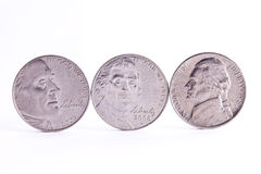 Three Nickel faces. Standing on the edge with white background Royalty Free Stock Images