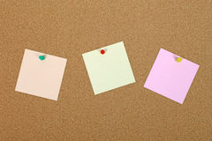 Three note paper on bulletin board. Three note papers attached to cork board with pins Royalty Free Stock Images