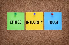 Three notes on corkboard with words Integrity, Trust, Ethics. stock image