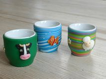 Three novelty eggcups on a wooden table Stock Photography