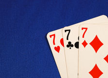 Three of the number seven cards. Concepts of Lucky Sevens isolated on blue stock photo