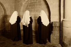 Three nuns in church. Three nuns in habit standing in a medieval abbey royalty free stock photos