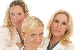 Three nurses medical females with happy expression. Group of three pretty nurses or doctors or medical professionals wearing nurse's scrub clothes and lab coats Stock Images