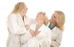 Three nurses medical females with happy expression. Group of three pretty nurses or doctors or medical professionals wearing nurse's scrub clothes and lab coats Royalty Free Stock Photos