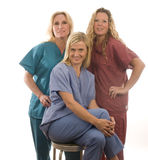 Three nurses in medical scrubs clothes Stock Photos