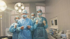Three nurses and a surgeon in the operating room after the operation is completed. Remove medical masks Stock Photo