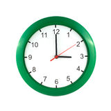 Three o'clock  on green wall clock. Three o'clock on big wall clock in green case isolated on white close up Royalty Free Stock Image