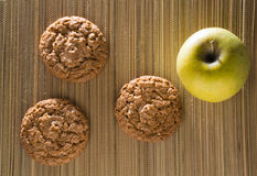 Three oatmeal cookies with apple on a bamboo mat.  Stock Photography