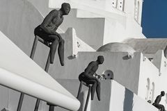Three Observer sculptures with Orthodox Metropolitan Cathedral in Fira, Santorini, Greece Stock Images