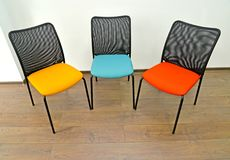 Three office chairs with color seats stand indoors Royalty Free Stock Photography