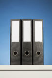 Three Office Folders. Three black office binders or folders on a white desk with blue background Royalty Free Stock Photography