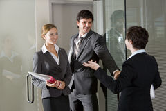Three office workers chatting at door of boardroom Stock Photography