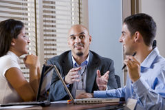 Three office workers conversing at desk stock photography