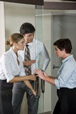 Three office workers at door of boardroom Stock Photo