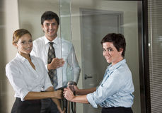 Three office workers at door of boardroom Royalty Free Stock Images
