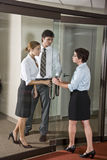 Three office workers at door of boardroom royalty free stock photography