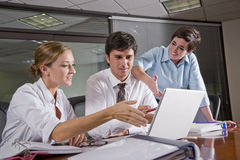 Three office workers working in boardroom stock images