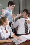 Three office workers working in boardroom Stock Photos