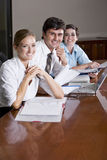 Three office workers working in boardroom Stock Image