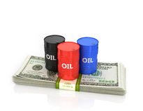 Three oil barrels on a pack of dollars. Stock Photos