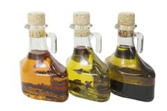 Three oils. Three olive oils in bottles lined up isolated against a white background Royalty Free Stock Photography