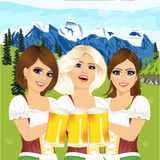 Three oktoberfest girls holding beer tankards against country scene with mountains Stock Photography
