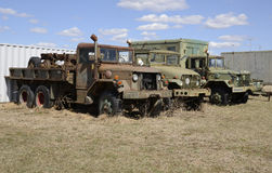 Three old army vehicles parked in a grass field Royalty Free Stock Photo