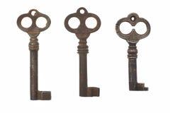 Three old antique keys on white background. Three old keys isolated on white background Stock Images