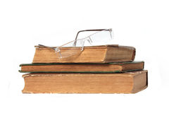 Three old books and glasses Stock Photo