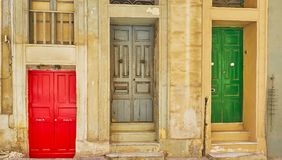 The old doors of Valletta homes, Malta. Three old bright colored doors in Old Mint street, the red one is lower than ground level and another two have some steps Royalty Free Stock Images