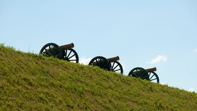 Three old guns on a green grass slope against the background of a clean sky. Three old cannons on a green grass slope against the background of a clean sky Royalty Free Stock Images