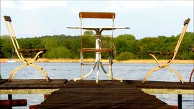 Three old chairs and one table on jetty stock footage