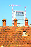 Three old chimney pot with modern construction in the background Royalty Free Stock Photography