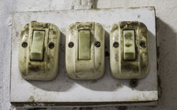 Three old and dirty light bulb switch Stock Photos