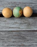 Three Old  Easter Eggs. Traditional Greek style painted hens eggs, three in a row  , Easter tradition , on shabby chic wooden bench Royalty Free Stock Images