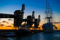 Port with old cranes and sailer in evening backlight with beautiful sunset and evening mood, Barbados, Caribbean Sea.