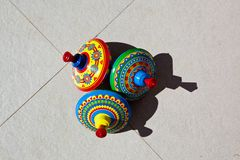Three old fashioned circus design tin spinning tops lie on the ground royalty free stock photos