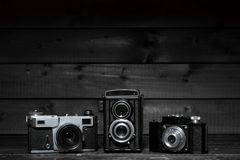 Three film cameras on a dark wooden background Royalty Free Stock Photography