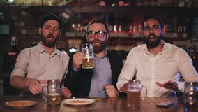 Three old friends drinking beer, cheering together in a pub. Football fans, friendship, sports concept. Three old friends drinking beer, cheering together in a stock video