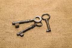 Three  old keys to the safe on a very old cloth Royalty Free Stock Image