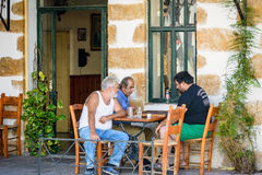 Three old men sitting at greek taverna and playing backgammon. VRYSOS, CRETE, GREECE - AUGUST 2015: Three old men sitting at greek taverna and playing backgammon Royalty Free Stock Image
